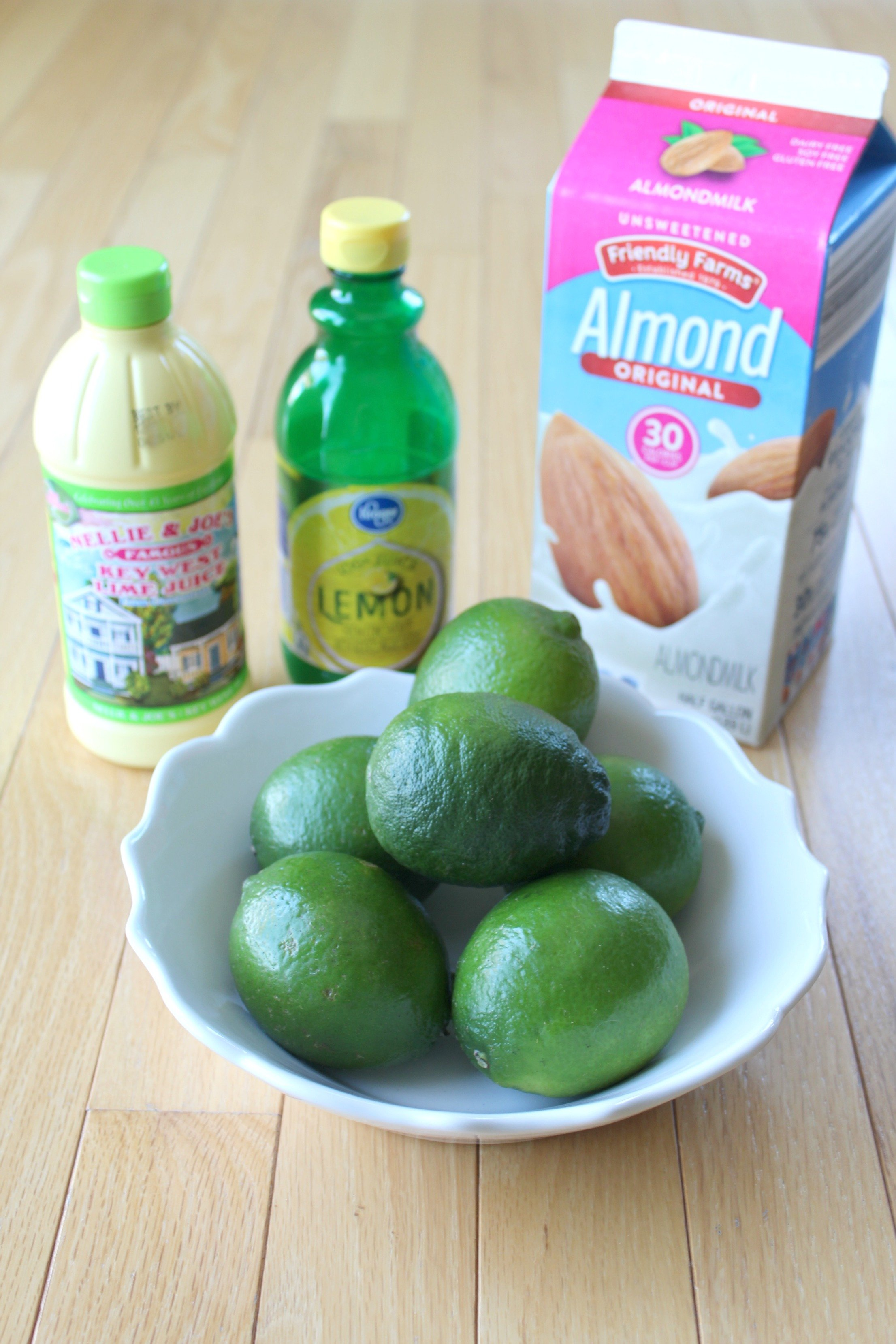 ingredients for lime dole whip with limes, almond milk, lemon juice and lime juice.