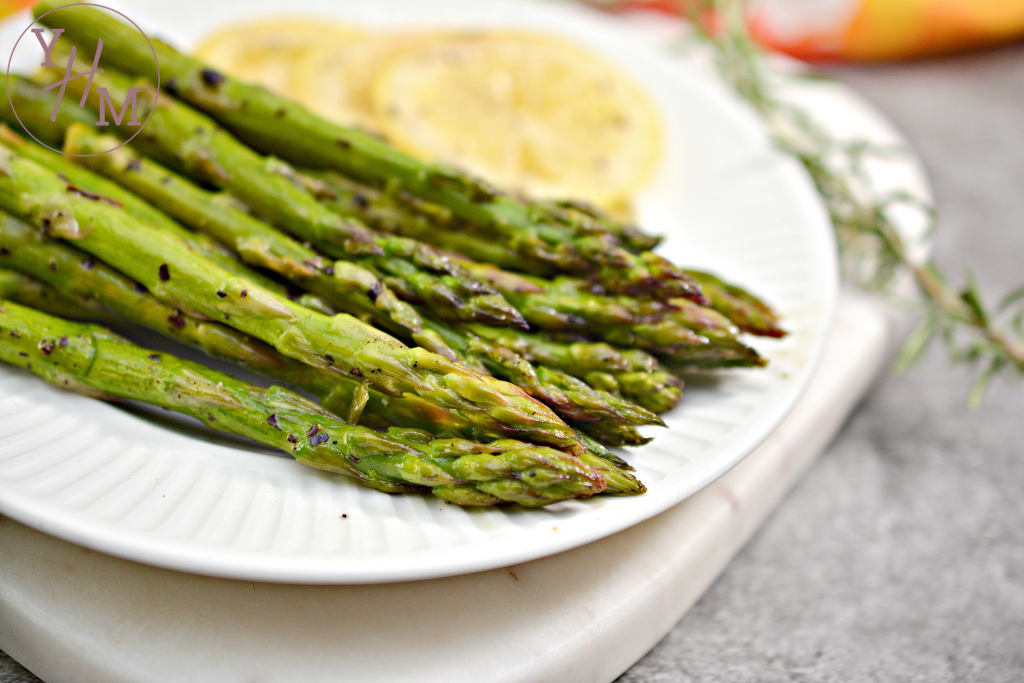 asparagus on white plate with slices of lemon