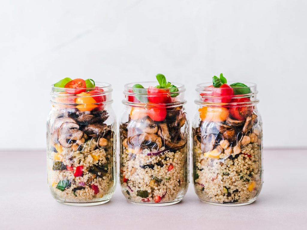 3 mason jars filled with vegetable quinoa, mushrooms and tomatoes with herbs